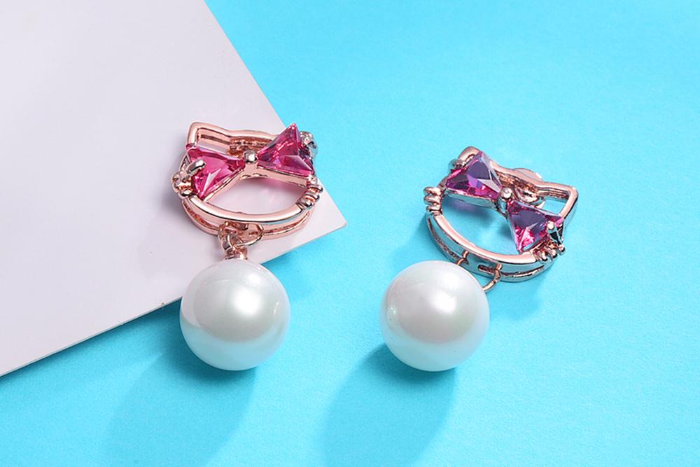 日系小貓珍珠鑲鑽 耳針/黏式耳環,桌上展示。