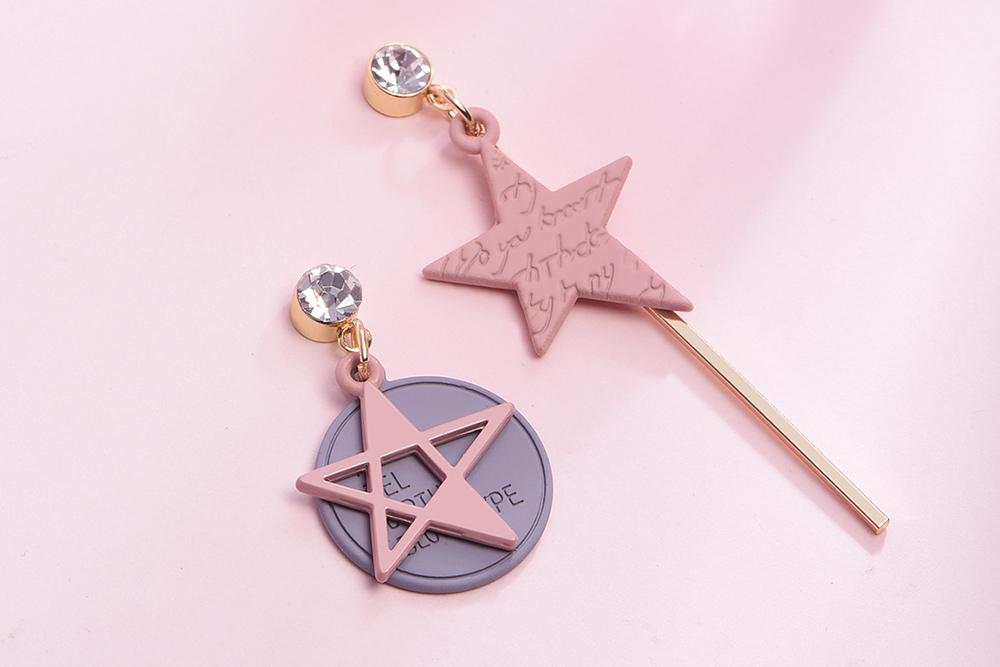 日系少女粉色五角星不對稱 耳針/黏式耳環,桌上展示。