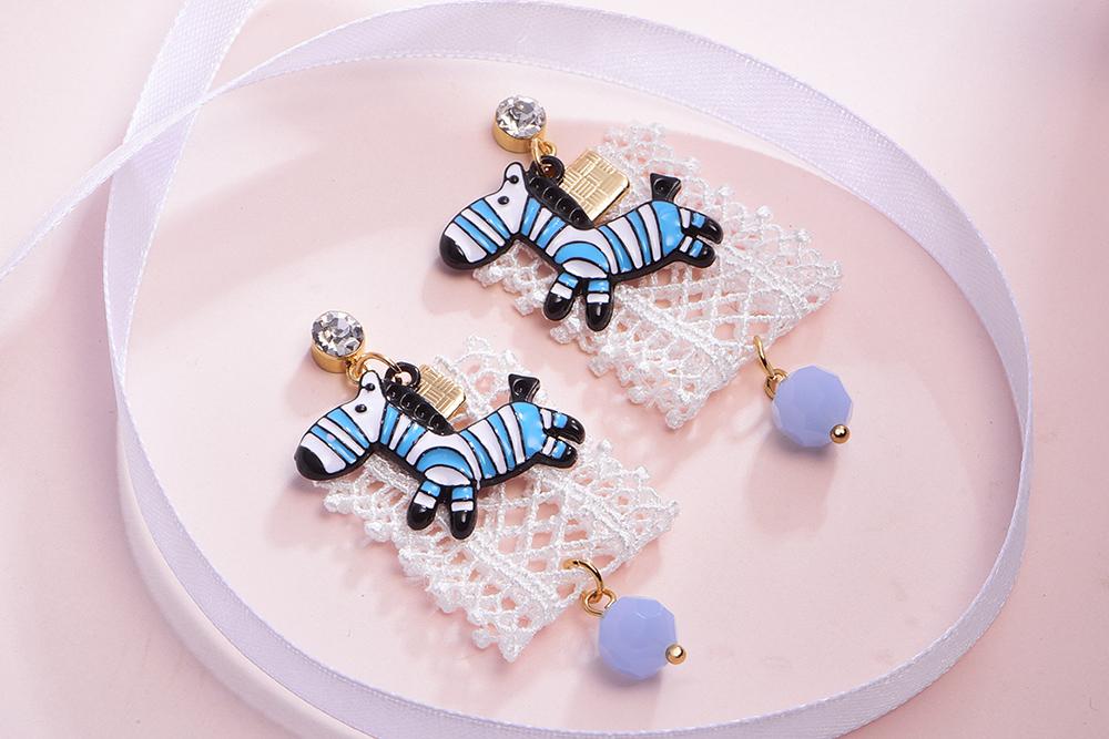 萌趣蕾絲藍色斑馬 耳針/黏式耳環,桌上展示。