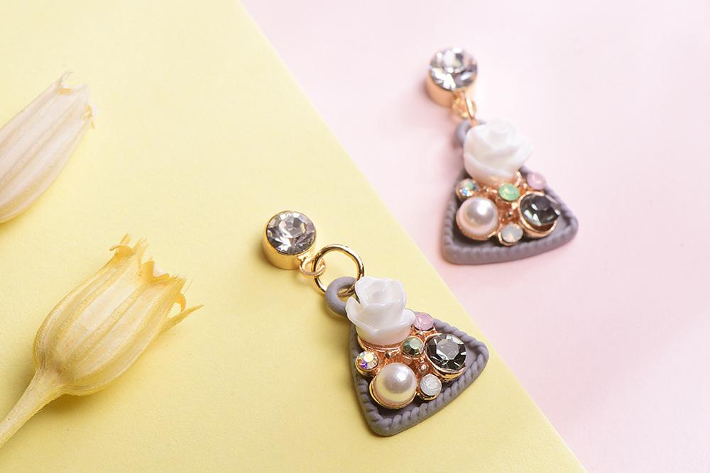 優雅絢爛珍珠花卉 耳針/黏式耳環,桌上展示。