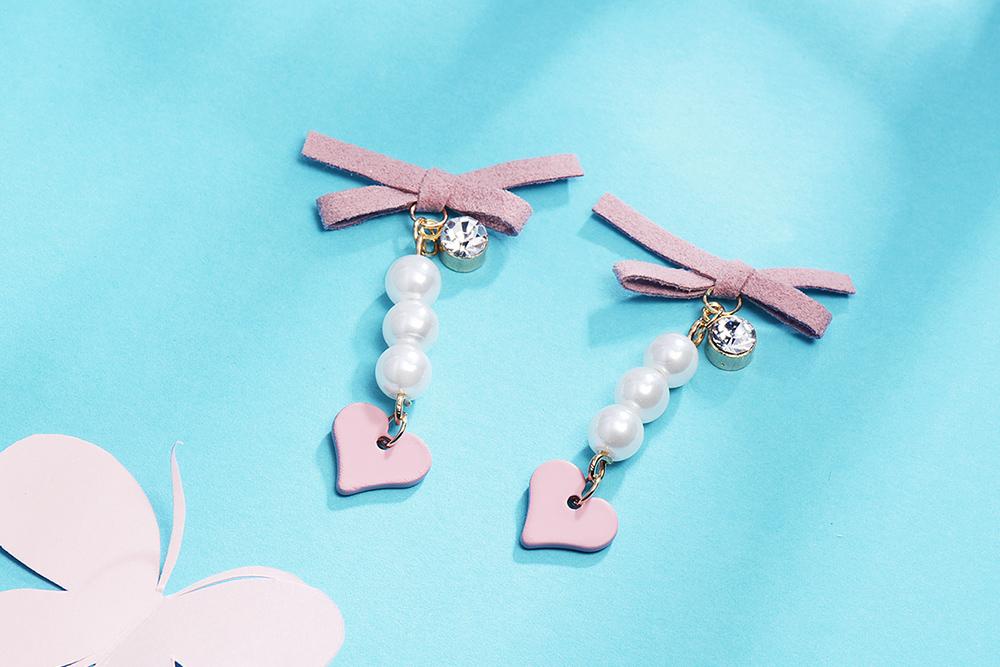 粉嫩蝴蝶結珍珠心型 耳針/黏式耳環,桌上展示。