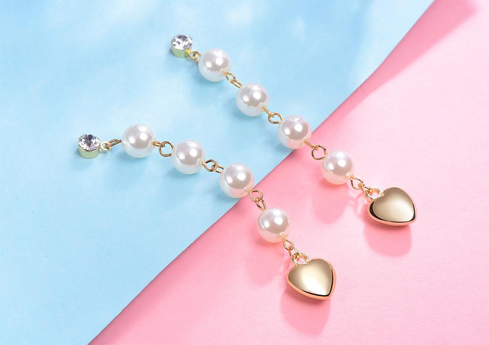 優雅珍珠流蘇金心黏式耳環,桌上展示。