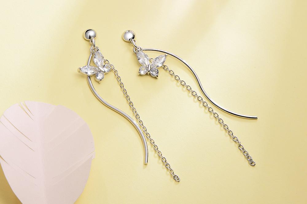 白金蝴蝶流蘇 耳針/黏式耳環,桌上展示。