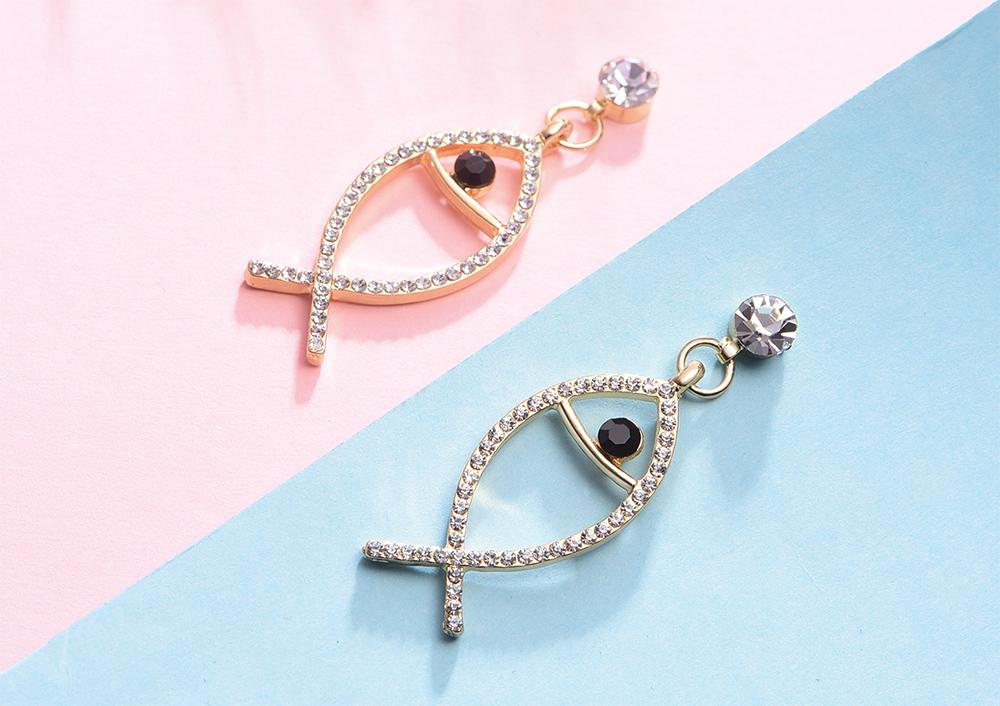 韓版氣質鑲鑽簍空小魚黏式耳環,桌上展示。