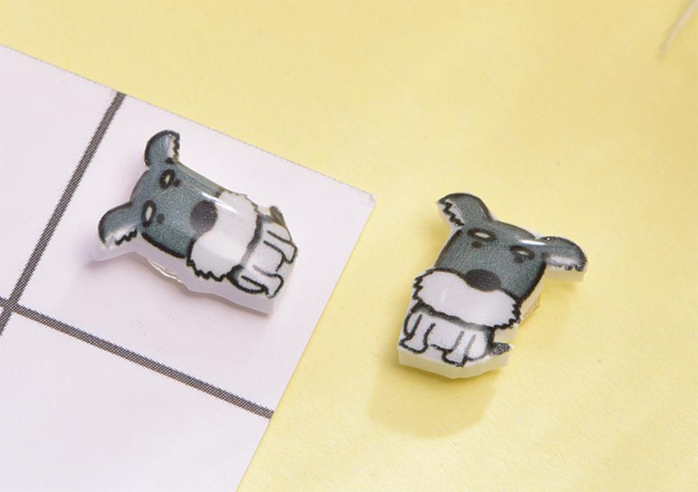 萌趣雪納瑞熱縮片黏式耳環,桌上展示。