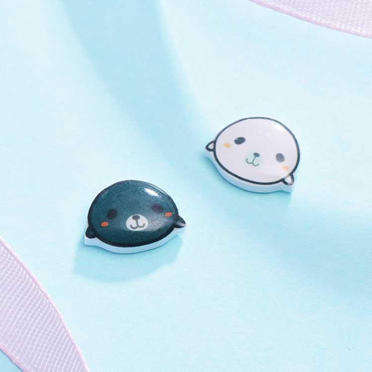 黑白海獺熱縮片黏式耳環,桌上展示。