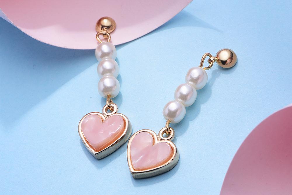 氣質簡約桃心珍珠 耳針/黏式耳環,桌上展示。