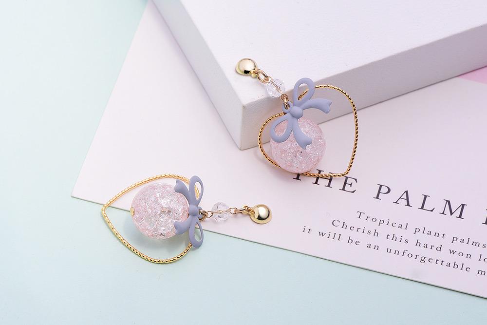 簍空金心裂紋珠蝴蝶結 耳針/黏式耳環,桌上展示。