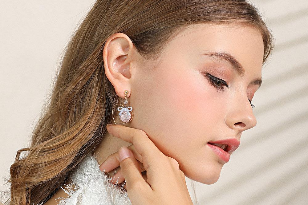 模特兒配戴展示:簍空金心設計,裂紋珠與可愛蝴蝶結點綴,優雅迷人,輕鬆無負擔的創新黏貼式耳環,不用穿耳洞也可以免除長時間配戴耳夾/夾式耳環的不舒服感。