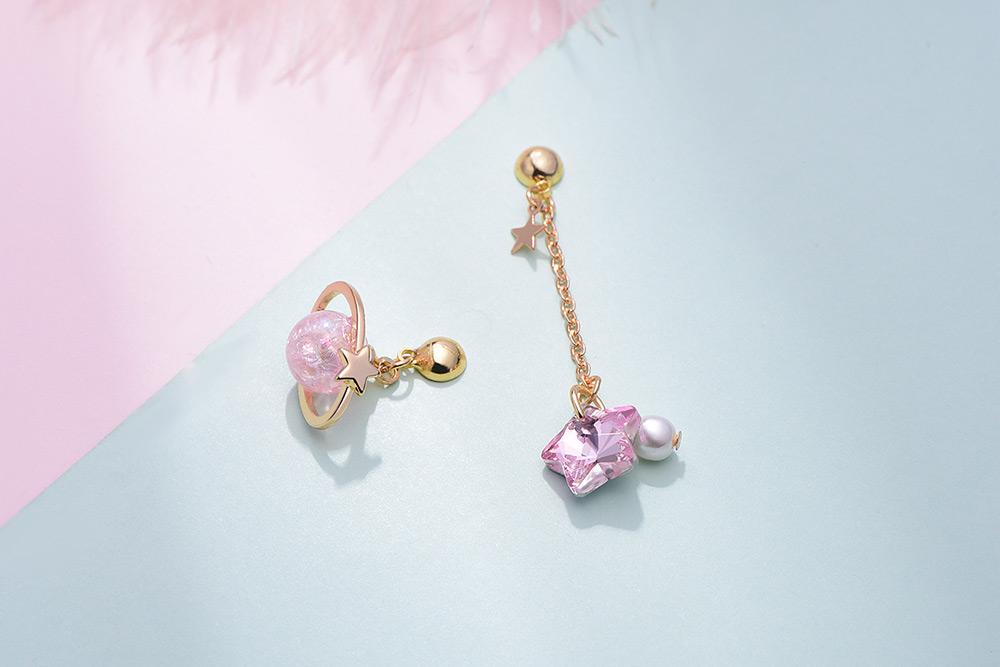 粉嫩星星宇宙不對稱 耳針/黏式耳環,桌上展示。