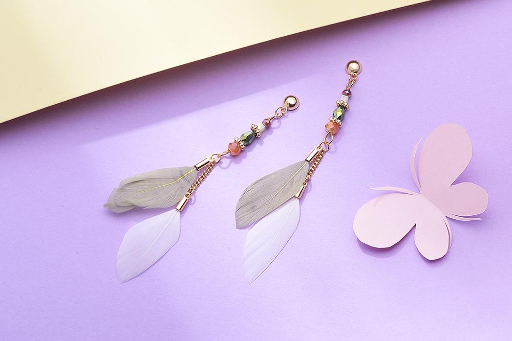 韓版長款氣質羽毛流蘇 耳針/黏式耳環,桌上展示。