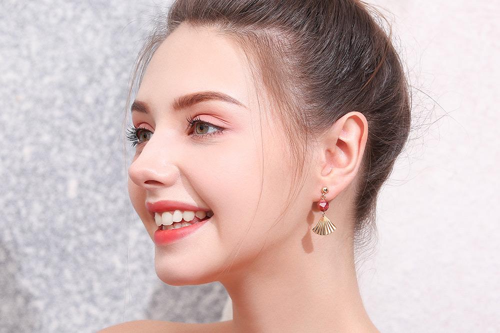 模特兒配戴展示:金色質感合金打造,簡約扇子造型,高雅的紅瑪瑙點綴更顯亮眼,全新研發黏貼式設計,免除穿/夾耳洞所造成的不適感,美美打扮更輕鬆。