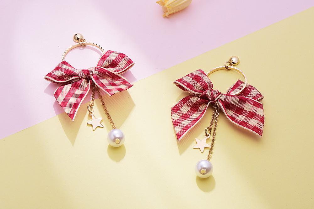 英格蘭紅格蝴蝶結 耳針/黏式耳環,桌上展示。