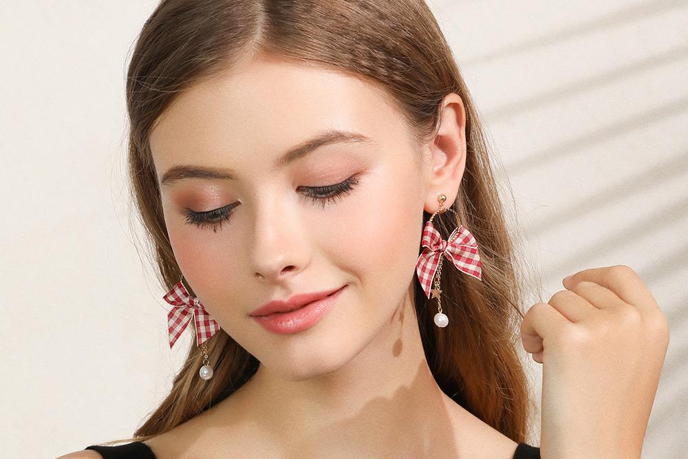 模特兒配戴展示:英格蘭紅格緞帶蝴蝶結,質感合金打造,潔白人造珍珠,散發出優雅的氣質,免穿耳洞的黏貼式設計,免除配戴耳夾/耳針的不適感,讓妳美美打扮輕鬆外出。