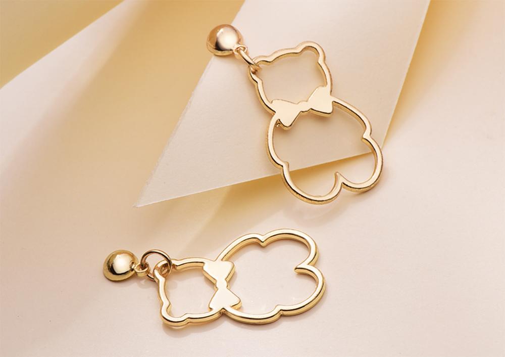 簍空金屬蝴蝶結小熊 黏式耳環,桌上展示。