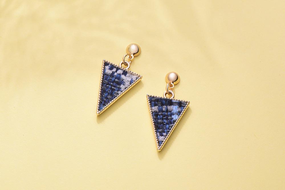 時尚棉麻編織三角形黏式耳環,桌上展示。