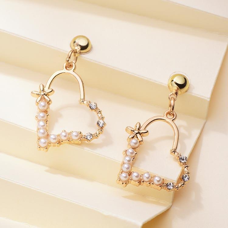 簍空珍珠愛心鑲鑽 黏式耳環,桌上展示。