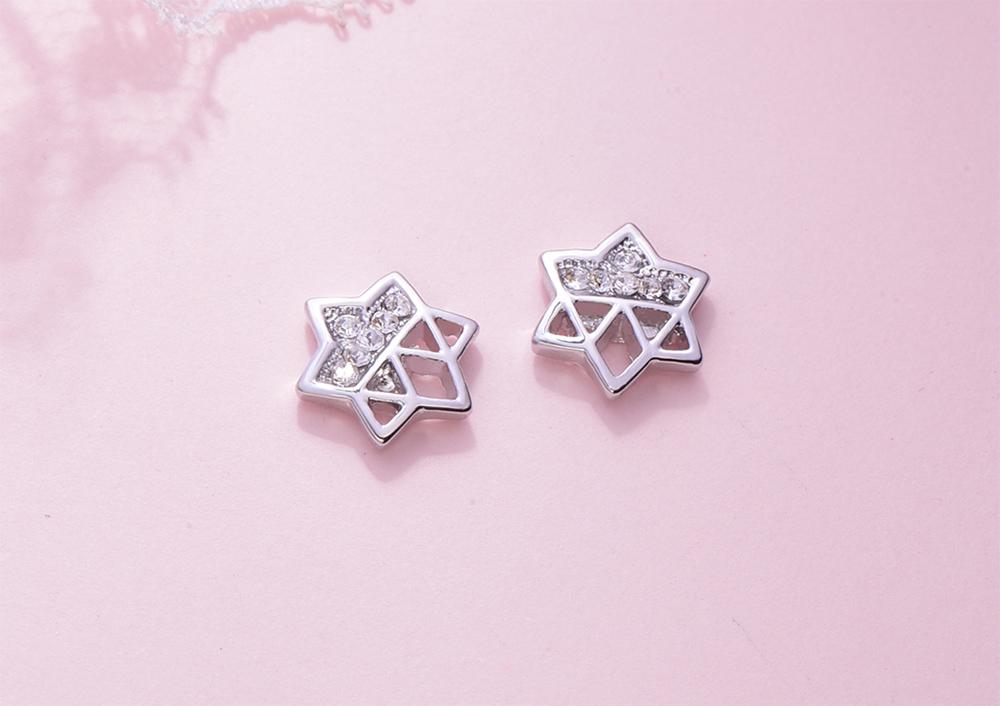 鏤空閃耀半鑽六芒星 黏式耳環,桌上展示。