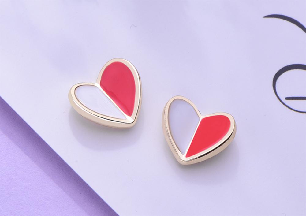 個性迷你拼色愛心 黏式耳環,桌上展示。