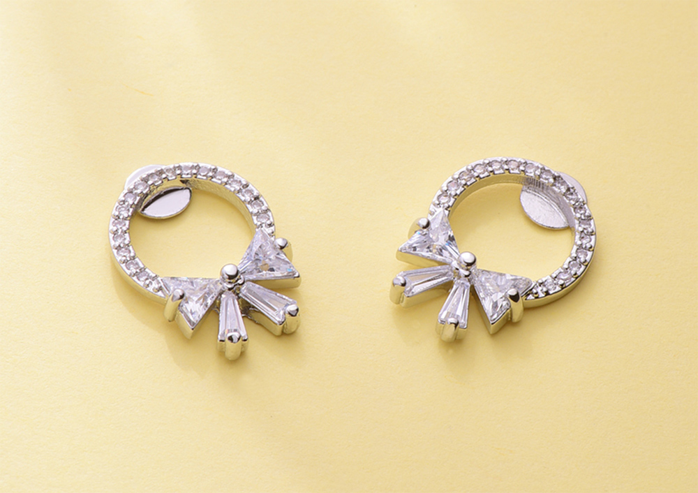 甜美氣質蝴蝶結鑲鑽 黏式耳環,桌上展示。