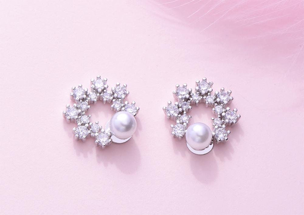 優雅珍珠花環鑲鑽 黏式耳環,桌上展示。