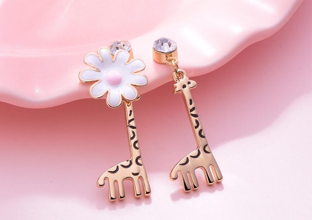 優雅花朵長頸鹿不對稱 耳針/黏式耳環,桌上展示。