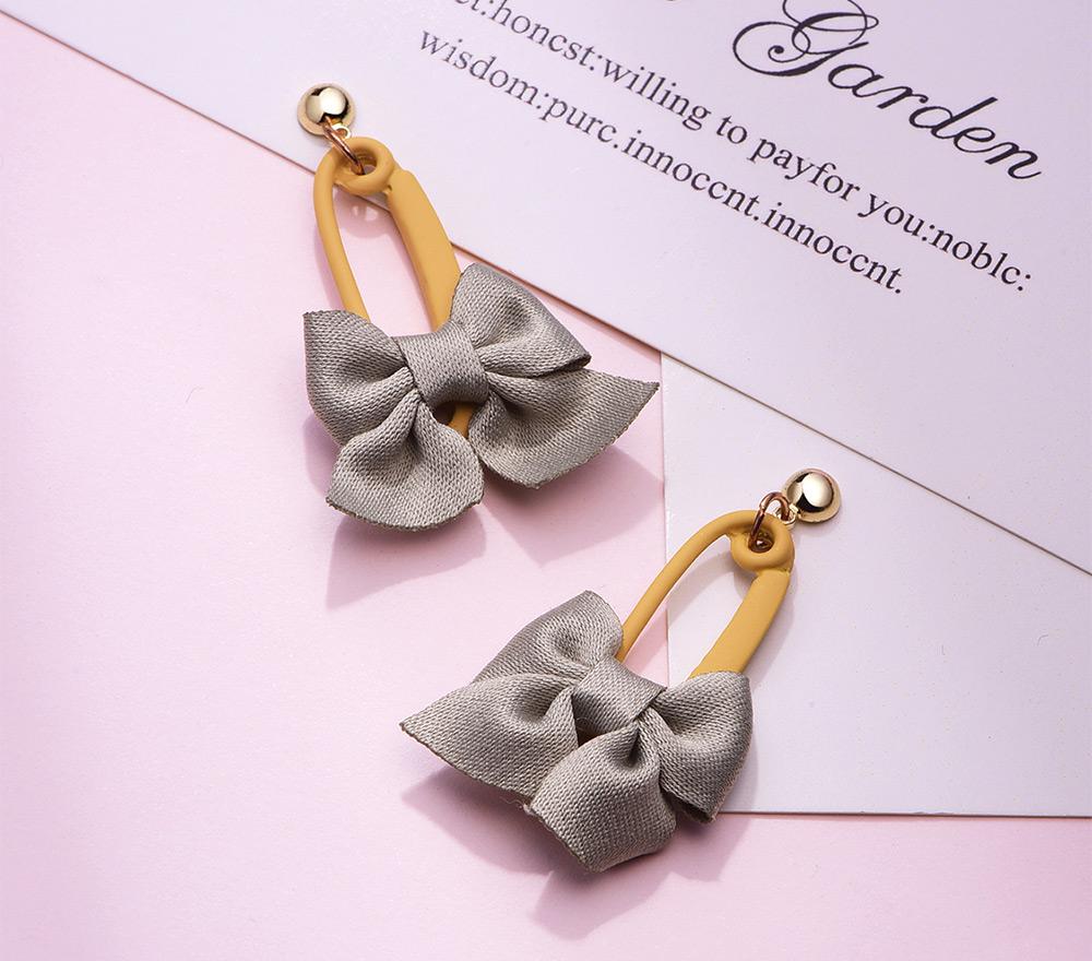 可愛馬卡龍色系蝴蝶結 耳針/黏式耳環,桌上展示。