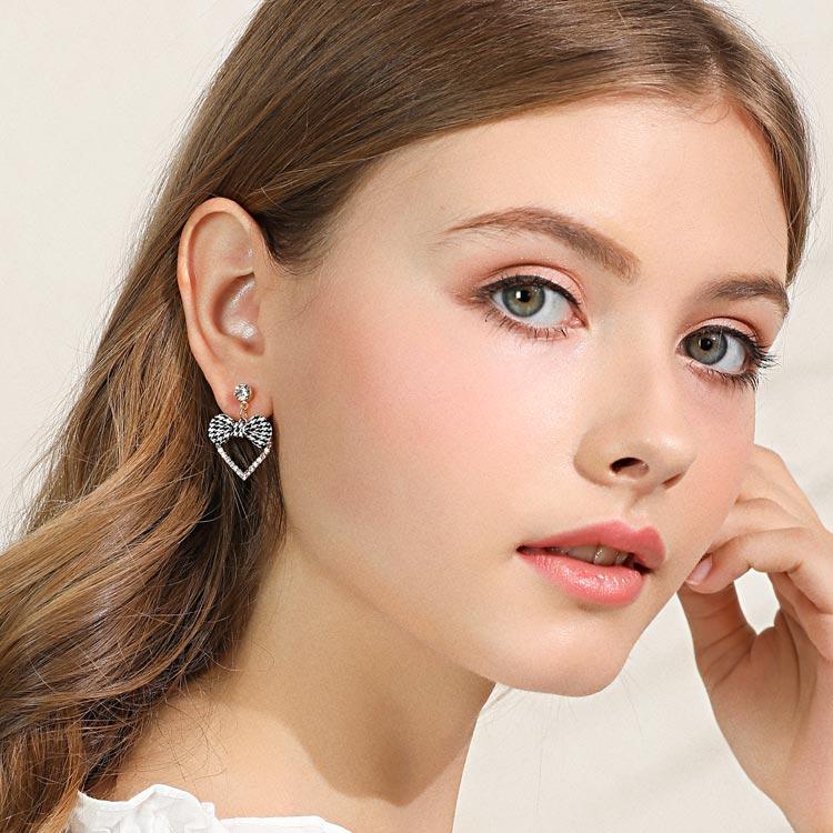 模特兒配戴展示:時尚簍空金屬愛心,黑格緞帶蝴蝶結,閃耀人造水鑽鑲嵌,耀眼迷人,免穿耳洞的黏貼式設計,免除配戴耳夾/耳針的不適感,讓妳美美打扮輕鬆外出。