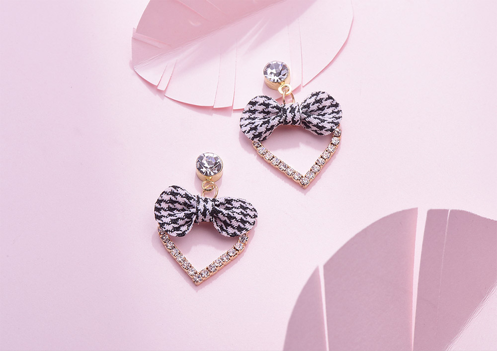 簍空心型黑格蝴蝶結 耳針/黏式耳環,桌上展示。