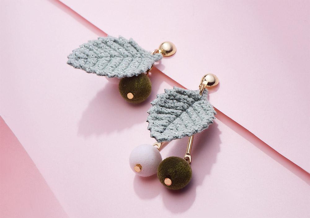 森系針織樹葉絨球不對稱 耳針/黏式耳環,桌上展示。