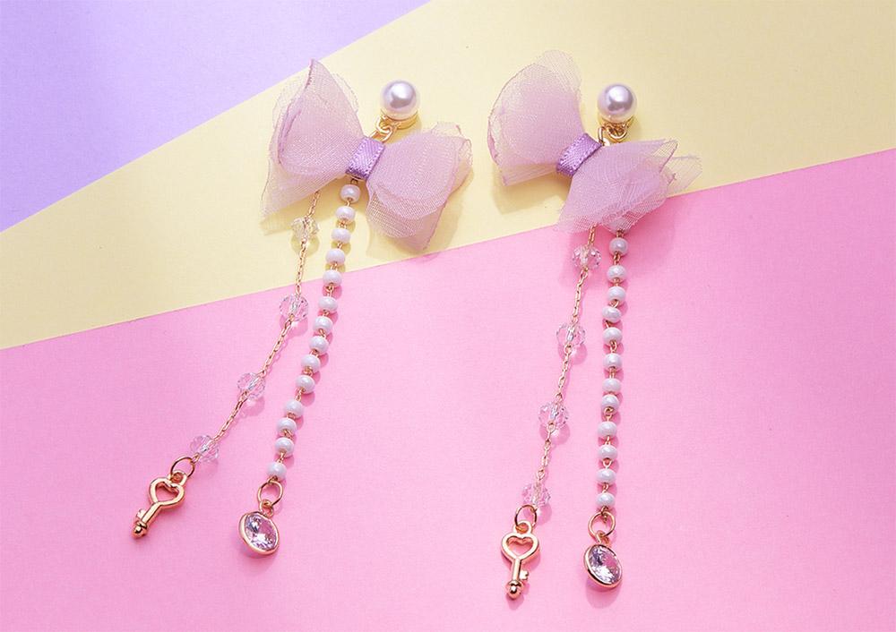 粉嫩珍珠蝴蝶結流蘇 耳針/黏式耳環,桌上展示。