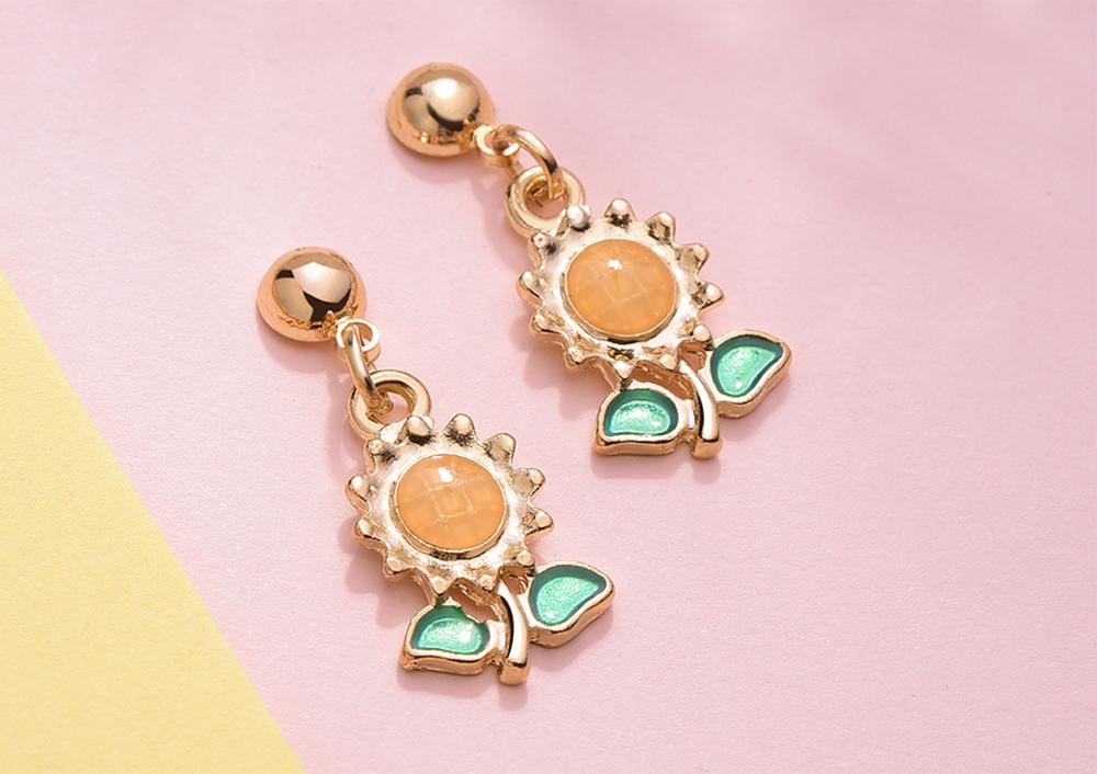 陽光耀眼向日葵 黏式耳環,桌上展示。