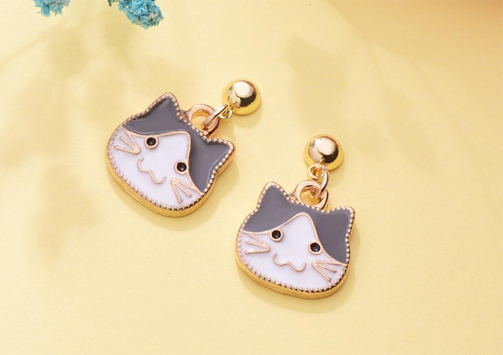 卡通小貓咪頭像黏式耳環,桌上展示。