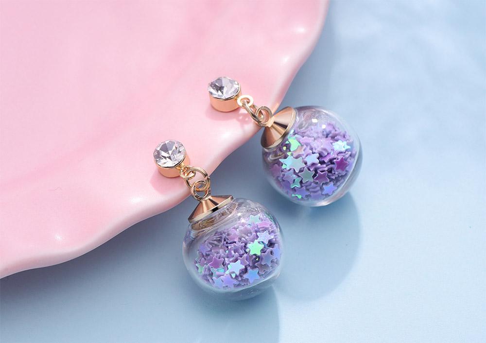 透明玻璃球閃耀亮片 耳針/黏式耳環,桌上展示。