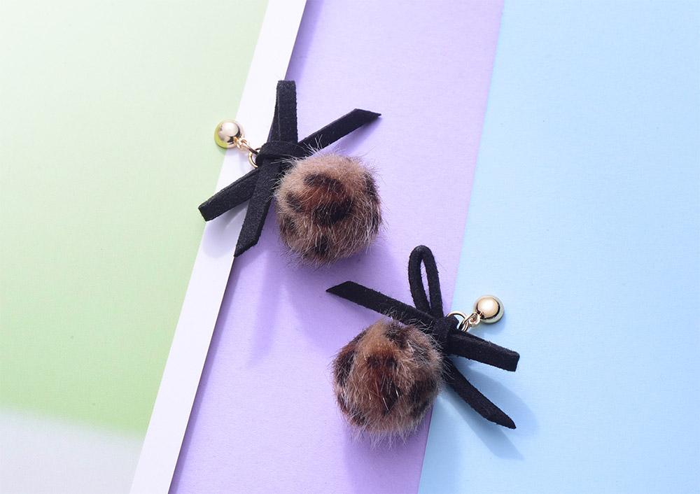 時髦蝴蝶結豹紋毛球 耳針/黏式耳環,桌上展示。