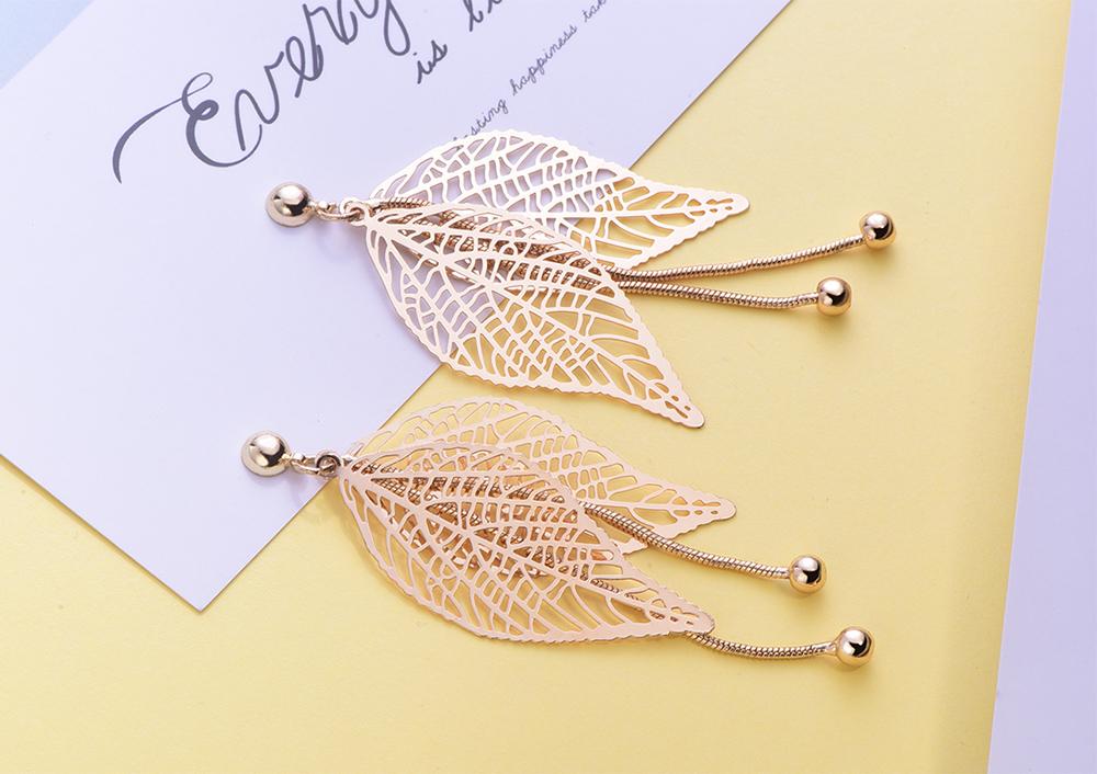 復古簍空長款樹葉流蘇 耳針/黏式耳環,桌上展示。