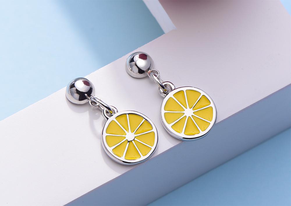 甜美小清新黃色檸檬 黏式耳環,桌上展示。