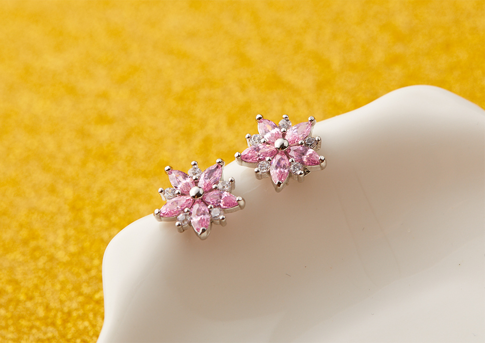 甜美粉嫩櫻花鑲鑽 黏式耳環,桌上展示。