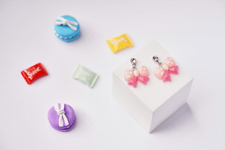 可愛圓點蝴蝶結黏式耳環,桌上展示。