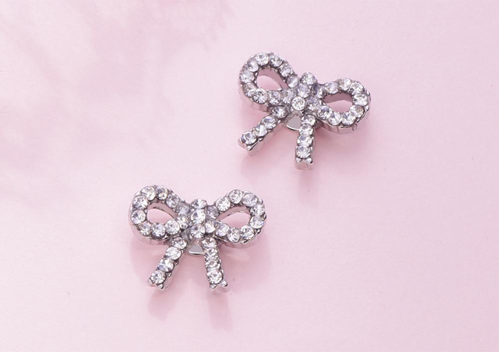 精緻小巧蝴蝶結滿鑽 黏式耳環,桌上展示。