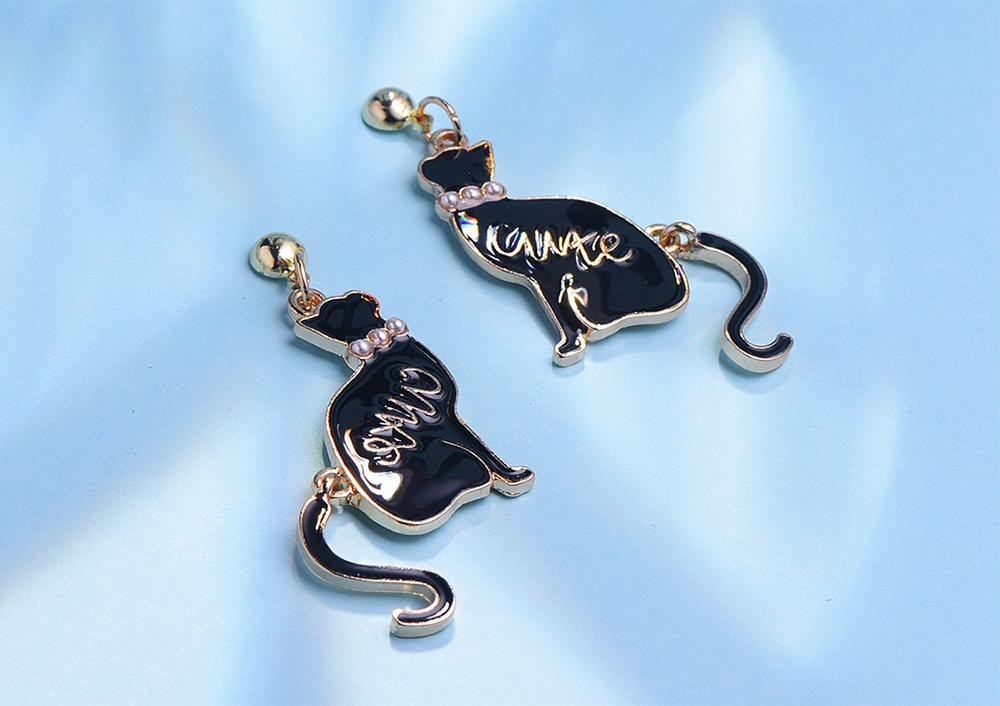 舞動珍珠黑色小貓 黏式耳環,桌上展示。