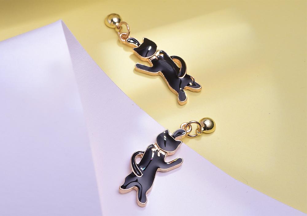 可愛緞帶黑色小貓 黏式耳環,桌上展示。