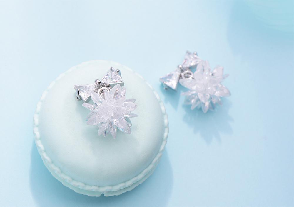 唯美清新雪花蝴蝶結 黏式耳環,桌上展示。