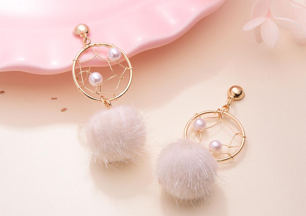 簍空捕夢網毛球黏式耳環,桌上展示。