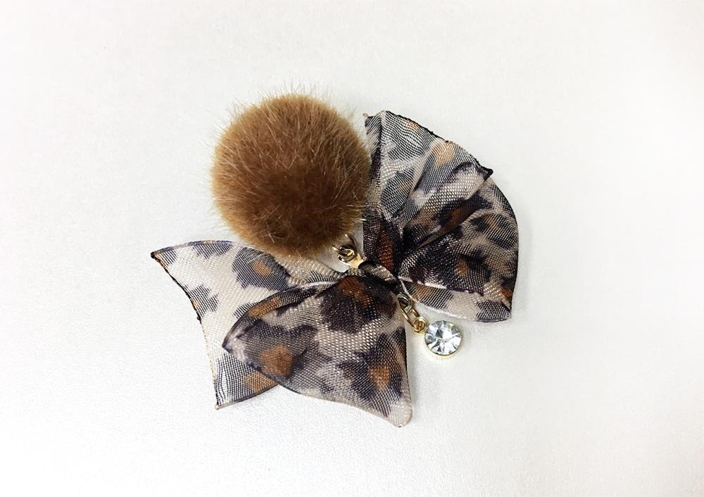 清新蝴蝶結緞帶毛球黏式耳環,桌上展示。