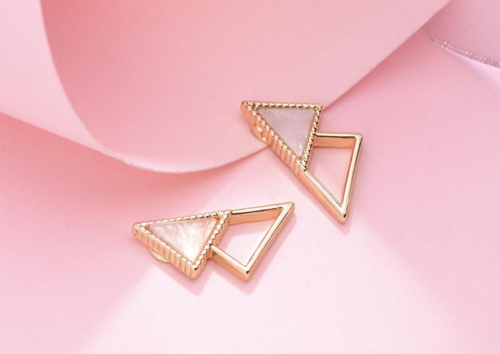 簡約個性幾何三角形黏式耳環,桌上展示。