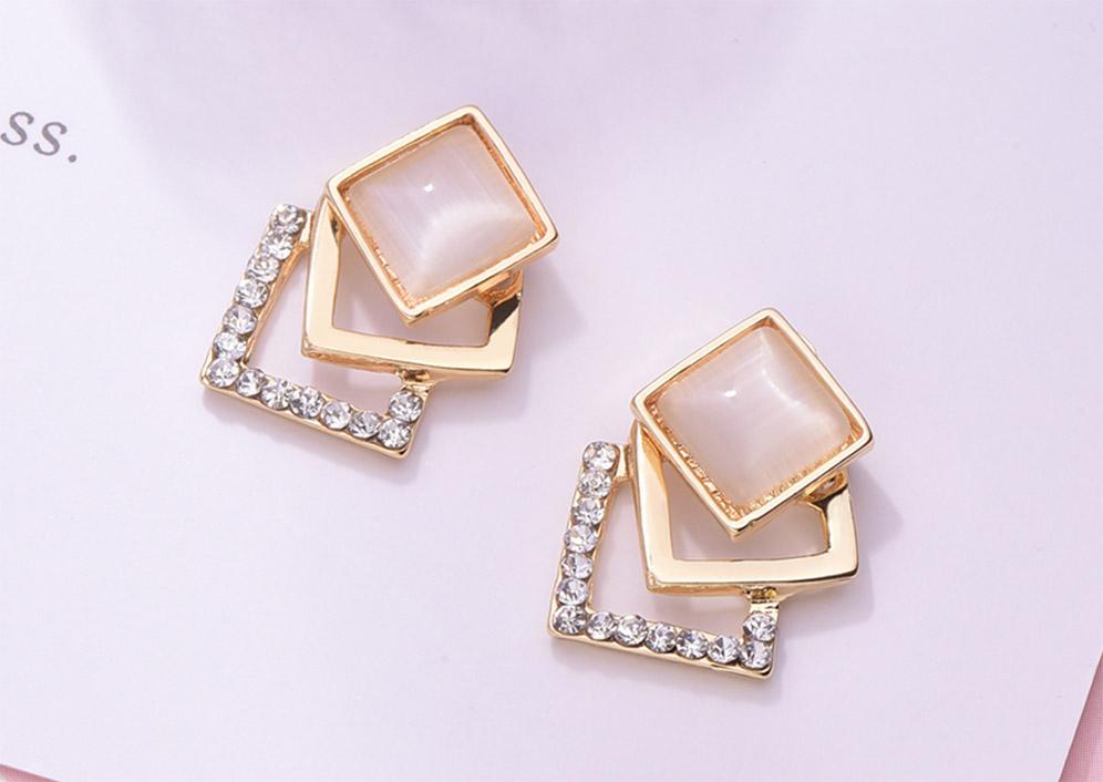 優雅菱形貓眼石鑲鑽 耳針/黏式耳環,桌上展示。