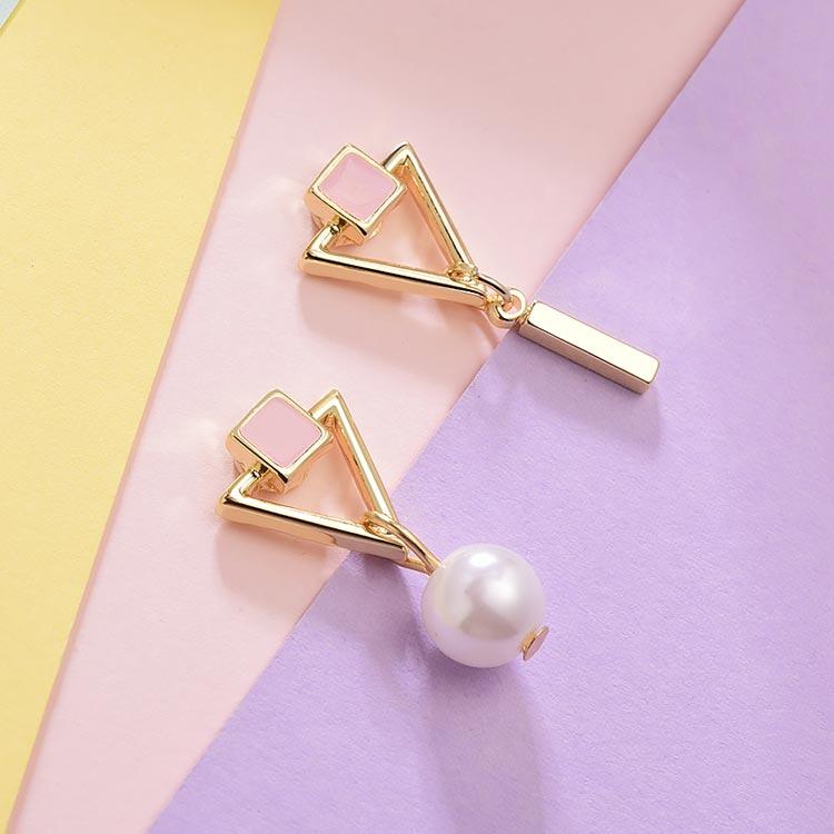 不對稱三角幾何珍珠 黏式耳環,桌上展示。