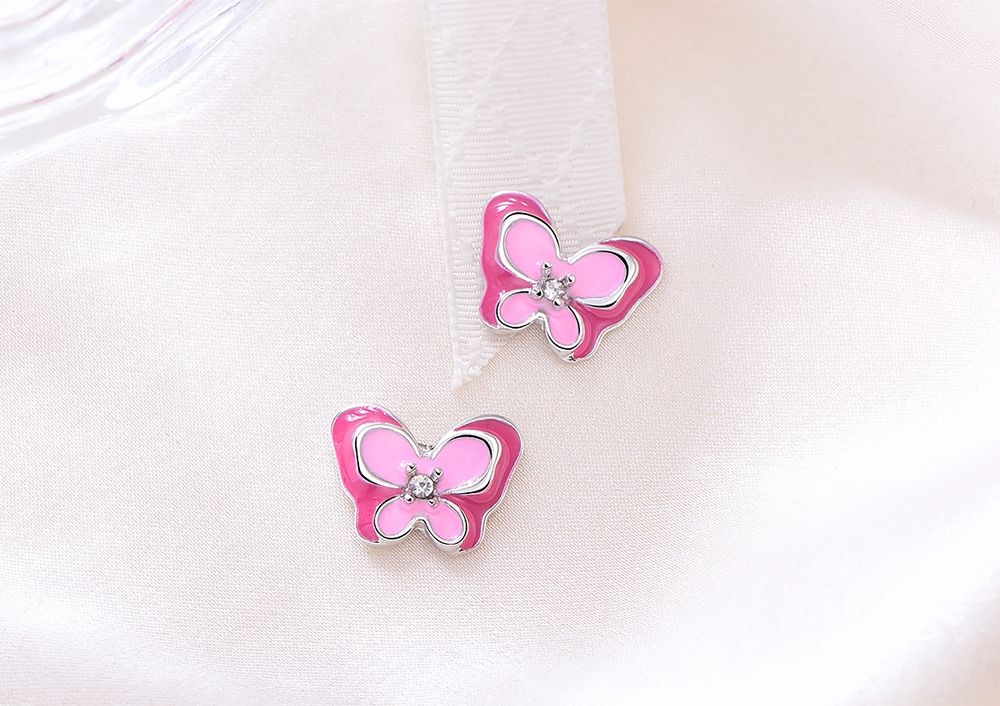 桃粉鑲鑽雙層蝴蝶 黏式耳環,桌上展示。