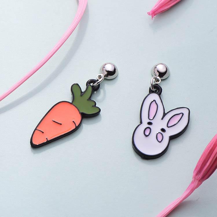 卡通白兔與胡蘿蔔不對稱 黏式耳環,桌上展示。